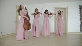 Quarteto fêmea que joga carismàtica em instrumentos amarrados na sala video estoque