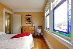 Quarto amarelo com o aparelhador branco da cama e da madeira. fotos de stock