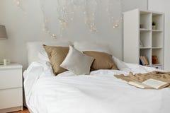 Quarto com cama e festão do Natal em casa imagem de stock