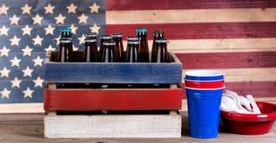 Quarto de julho com artigos da cerveja e do partido na madeira rústica Foto de Stock Royalty Free