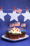 Bandeiras americanas dos EUA com as estrelas que penduram dos Pegs em uma linha e dos queques com espaço da cópia - vertical. Fotografia de Stock