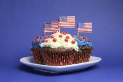 Quarto 4o da celebração do partido de julho com os queques vermelhos, brancos e azuis do chocolate Fotografia de Stock Royalty Free