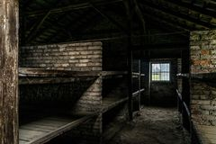 Quartos do sono com as camas de beliche de madeira que mostram a prisioneiros condições de vida terríveis no campo de concentraçã imagens de stock royalty free
