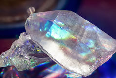 Quartz Crystal Rainbows. A quartz crystal point and another crustal casting prismatic shadows on a reflective surface Royalty Free Stock Photography