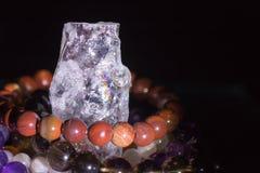 Quartz geode with semiprecious gemstone bracelets charging, spirituality concept, alternative medicine Stock Photos