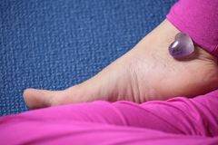 Quartz heart on a woman's foot. Practicing yoga Royalty Free Stock Photo
