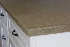 Quartz Kitchen Counter Top. Detail of quartz kitchen counter top with white cabinets stock photos