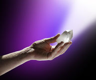 Quartz Wand in Magenta White Light. Male Hand holding a clear terminated quartz wand on a purple and black graduated background, with a shaft of light beaming Stock Photo