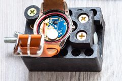 Quartz wristwatch prepared for replacing battery. Watch repairer workshop - open quartz wristwatch in holder prepared for replacing battery on wooden table close royalty free stock photography
