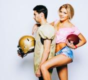 Quaterback в спорт равномерных при шлем представляя с чирлидером подруги, красивой блондинкой в шортах джинсовой ткани и Стоковые Фотографии RF