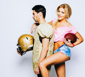 Quaterback dans les sports uniformes avec un casque posant avec une majorette d'amie, une belle blonde dans des shorts de denim e Photos libres de droits