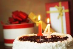 Quatorze anos de aniversário Bolo com vela e os presentes ardentes Imagens de Stock Royalty Free
