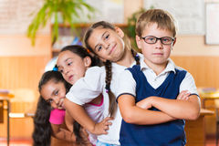 Quatre écoliers adorables se tenant dans la salle de classe Photos libres de droits