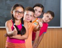 Quatre écoliers de sourire se tenant dans la salle de classe Photographie stock libre de droits