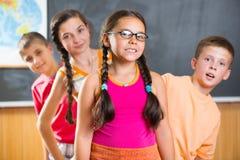 Quatre écoliers se tenant dans la salle de classe contre le tableau noir Image libre de droits