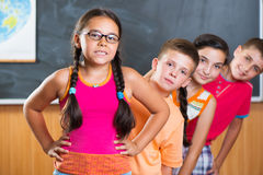Quatre écoliers se tenant dans la salle de classe contre le tableau noir Photographie stock libre de droits