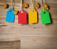 Quatre étiquettes colorées pour le texte et les fleurs de papier sur le bois. Images stock