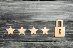 Quatre étoiles et un cadenas Le concept d'assigner la cinquième étoile, une limitation dans le rang Le désir d'obtenir la cinquiè image stock