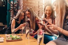 Quatre étudiantes de sourire s'asseyant dans le cafétéria causant utilisant des téléphones portables Images libres de droits