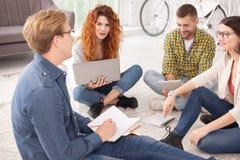 Quatre étudiants heureux discutant le projet Photos stock