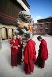 Quatre étudiants tibétains de lama avant un monastère Photographie stock