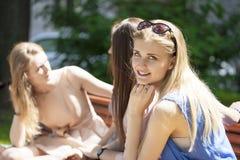 Quatre adolescentes s'asseyant sur le banc en parc d'été Image stock