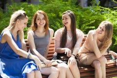Quatre adolescentes s'asseyant sur le banc en parc d'été Photographie stock libre de droits