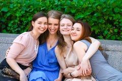 Quatre adolescentes s'asseyant sur le banc en parc d'été Photo stock
