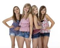 Quatre adolescentes sur le blanc Photographie stock