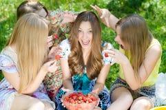 Quatre adolescents et fraises heureux Images stock