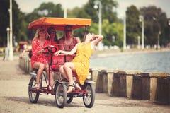 Quatre amie sur un vélo de touristes Photos stock