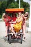 Quatre amie sur un vélo de touristes Photographie stock