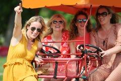 Quatre amie sur un vélo de touristes Photographie stock libre de droits
