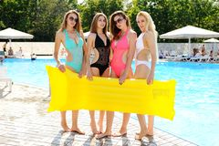 Quatre amies attirantes dans le maillot de bain coloré avec le matelas gonflable jaune à l'arrière-plan de piscine Image libre de droits