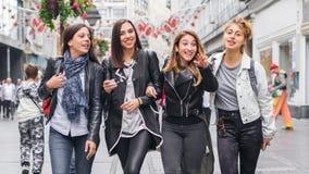 Quatre amies, bavardage et amusement de avoir sur la rue Photo stock