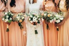Quatre amies et une jeune mariée tiennent de beaux bouquets de mariage dedans Photo stock