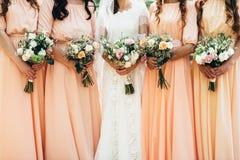 Quatre amies et une jeune mariée tiennent de beaux bouquets de mariage dedans Image libre de droits