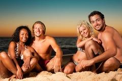 Quatre amis à la plage de coucher du soleil Photos libres de droits