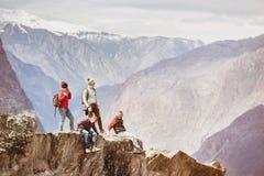 Quatre amis actifs sur le dessus de montagne de falaise Photos stock