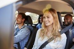 Quatre amis adultes heureux dans une voiture sur un voyage par la route Photographie stock