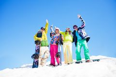 Quatre amis avec des surfs des neiges se tenant dans la neige Photographie stock