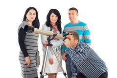 Quatre amis ayant l'amusement avec le télescope Photos libres de droits