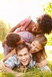 Quatre amis ayant l'amusement ensemble dans la campagne Image stock