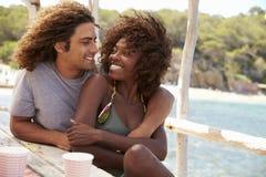Quatre amis ayant l'amusement se reposant à une table par la mer, Ibiza Images stock