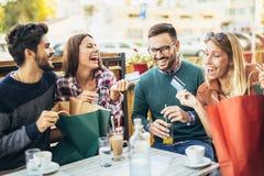 Quatre amis ayant l'amusement un café ensemble après l'achat Photographie stock libre de droits