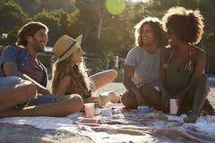Quatre amis ayant un pique-nique sur la plage, fusée de lentille, Ibiza Photos stock