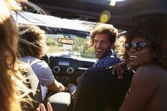 Quatre amis conduisant dans une voiture à couvercle serti, passager arrière POV Images libres de droits