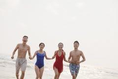 Quatre amis courant dans l'eau sur une plage sablonneuse Photo stock