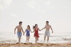 Quatre amis courant hors des mains de retenue d'eau sur une plage sablonneuse Photographie stock libre de droits