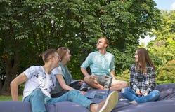 Quatre amis détendant en parc avec l'ordinateur portable Images stock